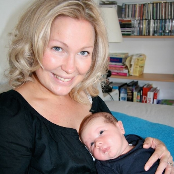 mother with blonde hair sitting holding baby