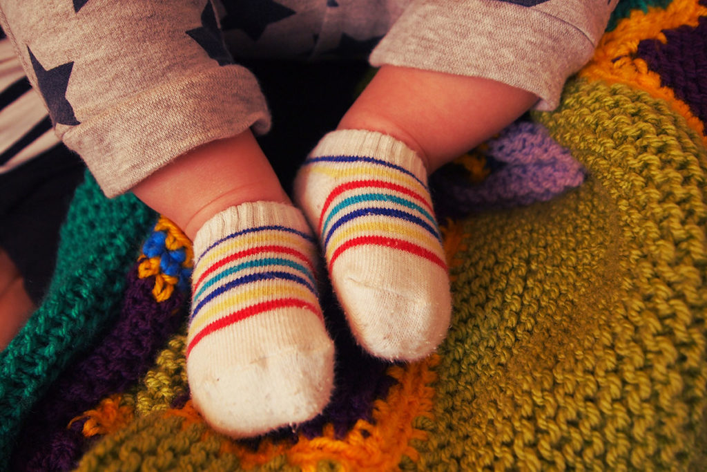 Baby's feet in rainbow striped socks against a coloured knitted blanket