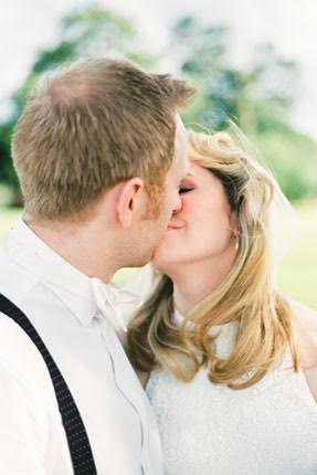 Patchwork couple kissing on wedding day outside