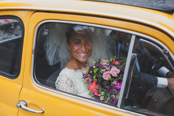 bride holding flowers in yellow car