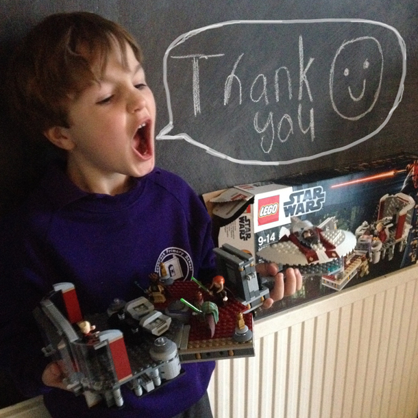 boy holding birthday gift Lego set thank you speech bubble