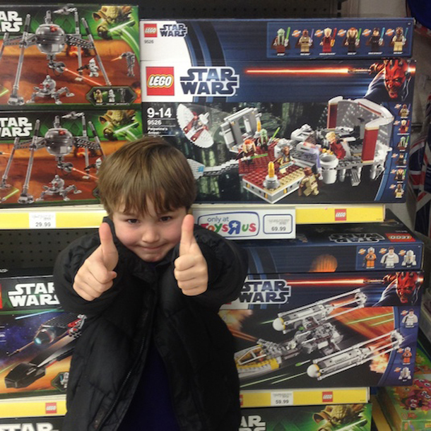 boy with thumbs up standing next to lego in shop