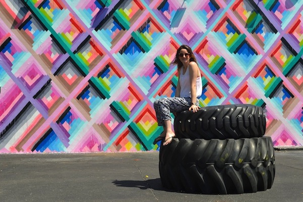 woman sitting on giant tyres Miami travel guide