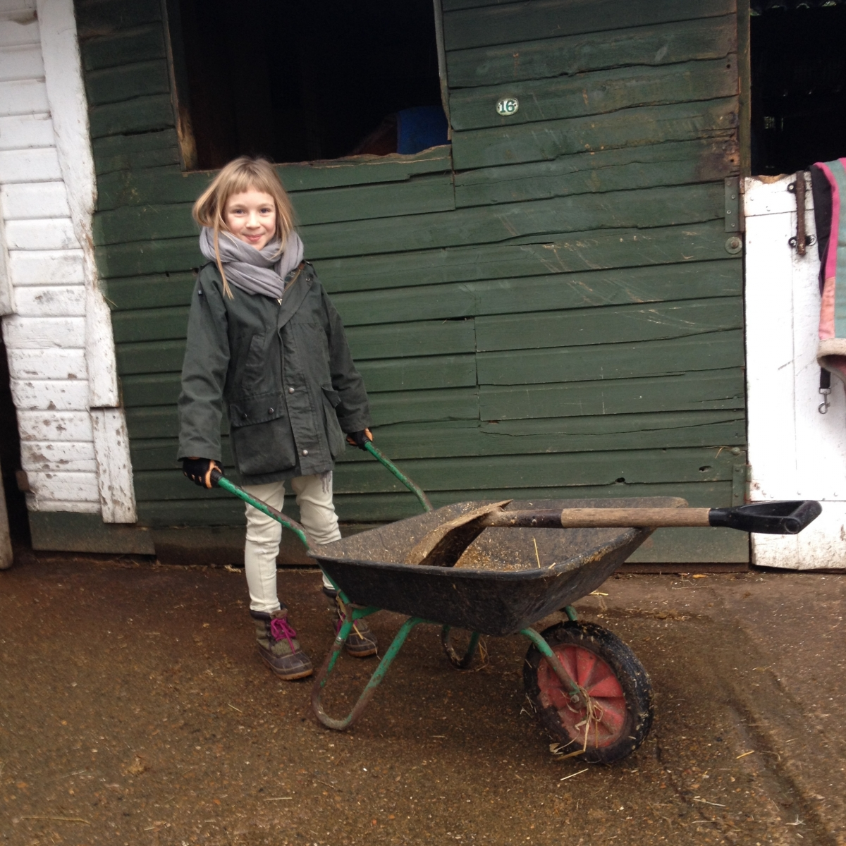 young girl with wheelbarrow at stables