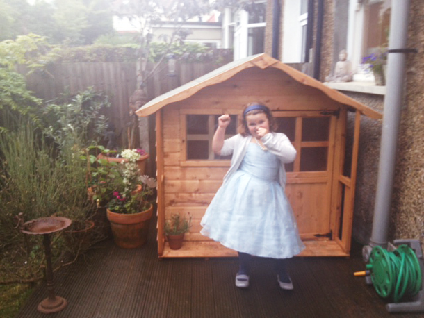 little girl standing next to her birthday gift playhouse funded with Patchwork