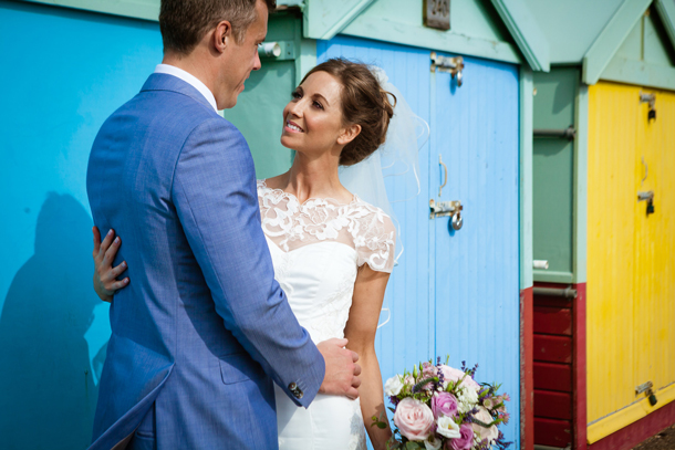 Patchwork couple in wedding wedding attire standing by beach huts