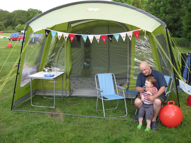 Man and little boy sitting next to tent in campfield
