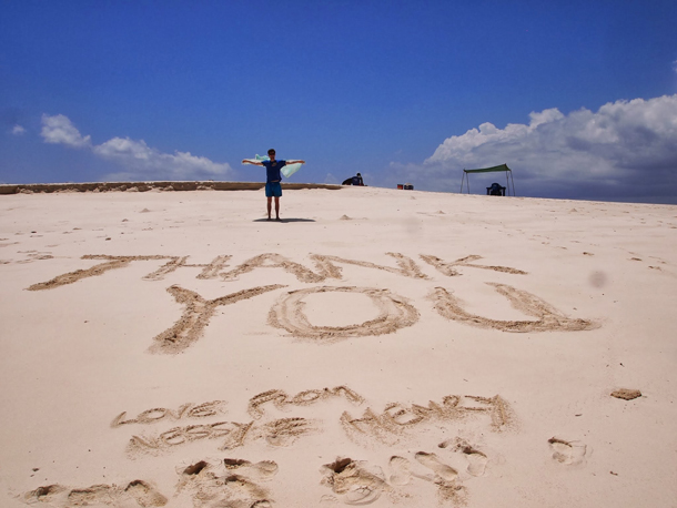 man on beach saying thank you for honeymoon adventure funded by friends