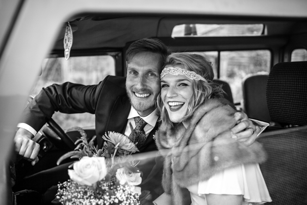 Patchwork couple with bride in vintage wedding dress looking out of car window