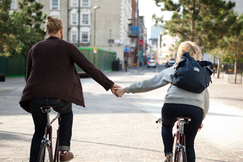 couple on bicycles holding hands