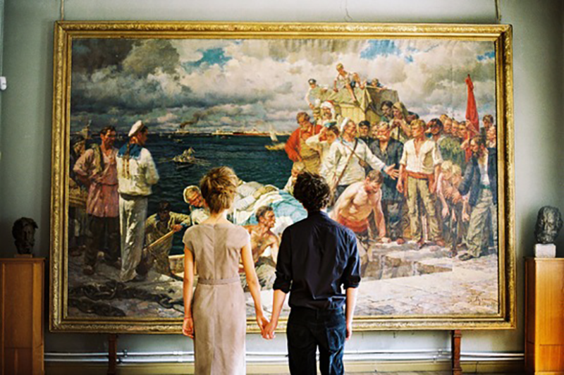 couple standing in from of large painting in art gallery