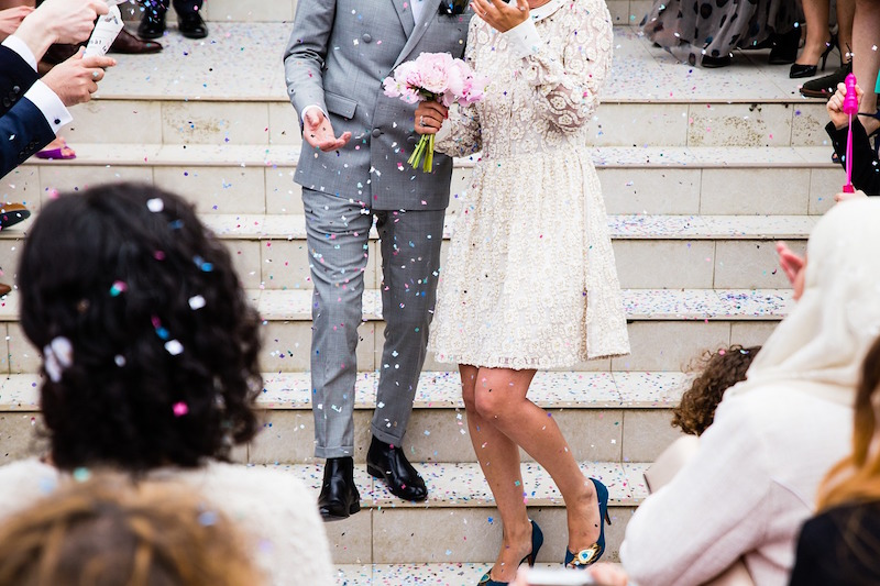 just married couple coming down steps in confetti shower