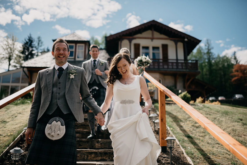 newlywed couple walking down steps and laughing