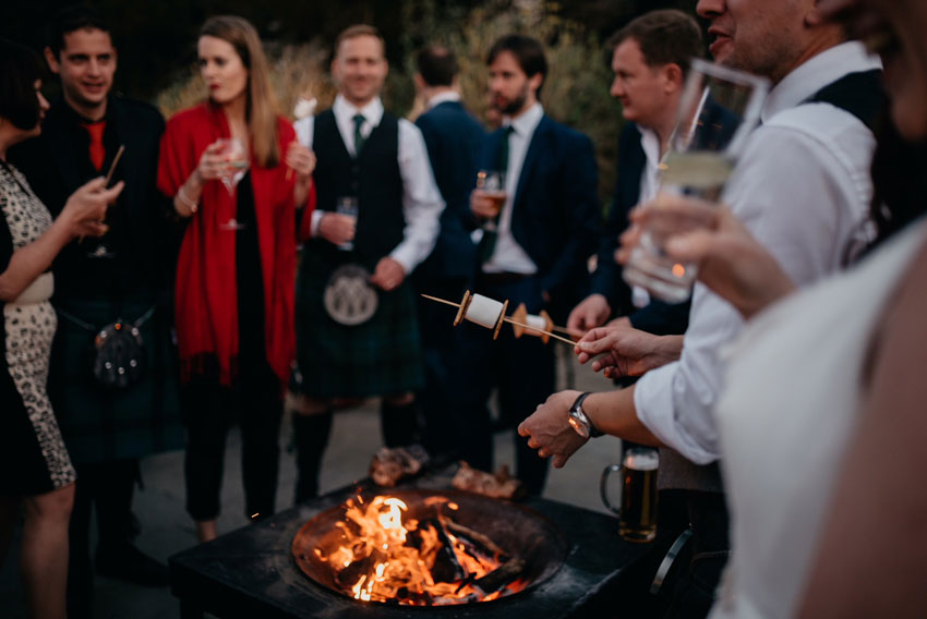 wedding-congregation-toasting-marshmallows-over-an-open-fire