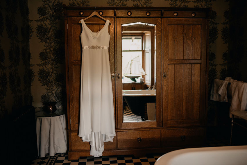 white wedding dress hung on old wooden wardrobe
