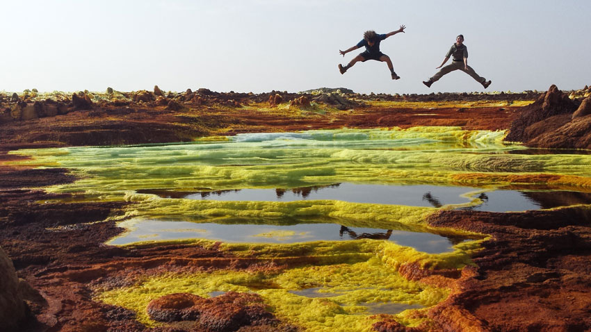 man-and-woman-doing-star-jumps-over-green-and-red-salt-flats-