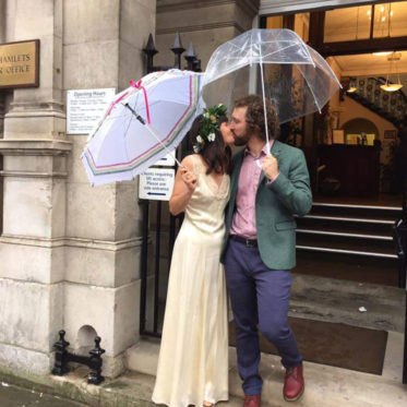 man-and-woman-kiss-on-steps-holding-umbrellas-