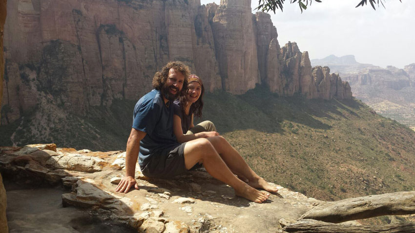 man-and-woman-sitting-on-the-edge-of-a-cliff
