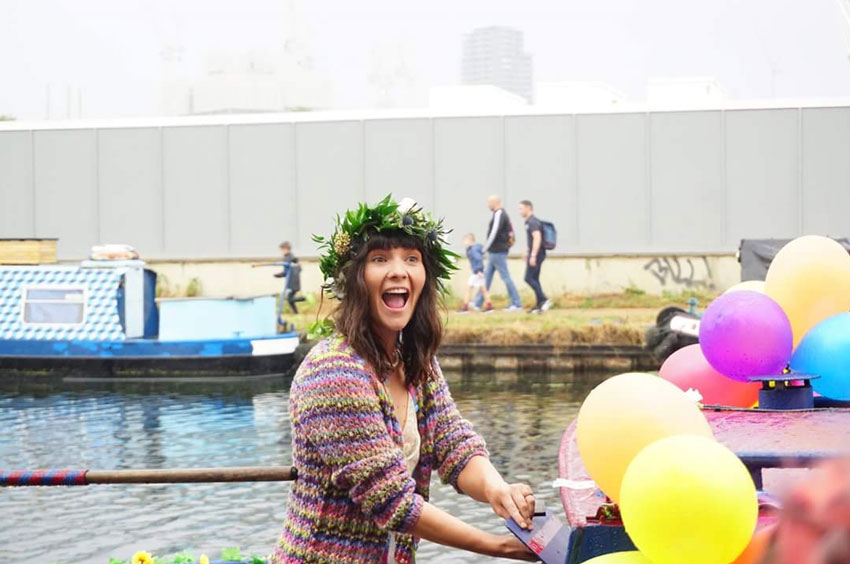 woman-smiling-on-back-of-canal-boat-covered-in-balloons