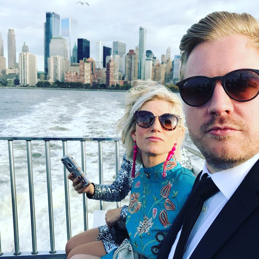 honeymoon couple in sunglasses on boat in front of new york skyline