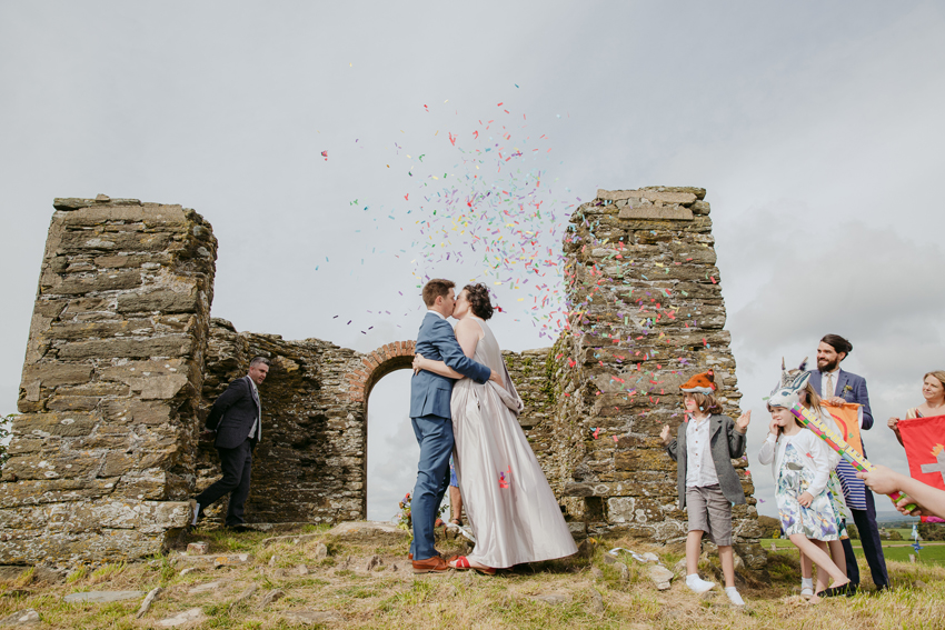 bride and groom kiss guests throw confetti