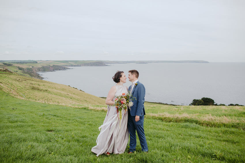 bride-and-groom-smile-at-each-other-with-cliff-and-sea-in-background