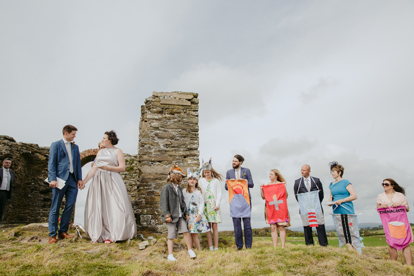 bride groom and wedding guests standing in field