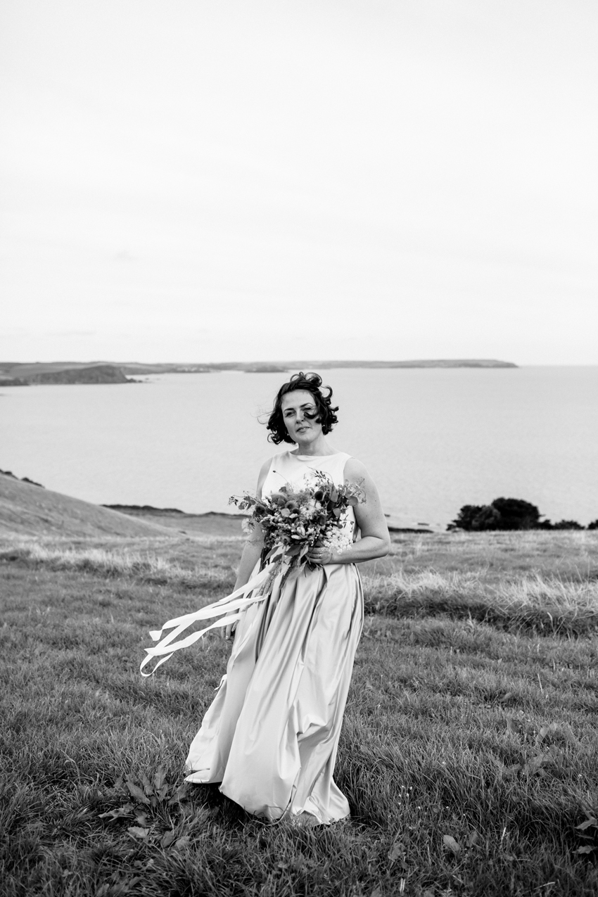 bride holding bouquet with sea in background