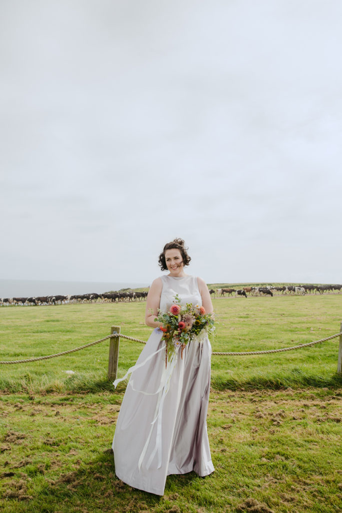 bride in wedding dress holding bouquet in field by cows