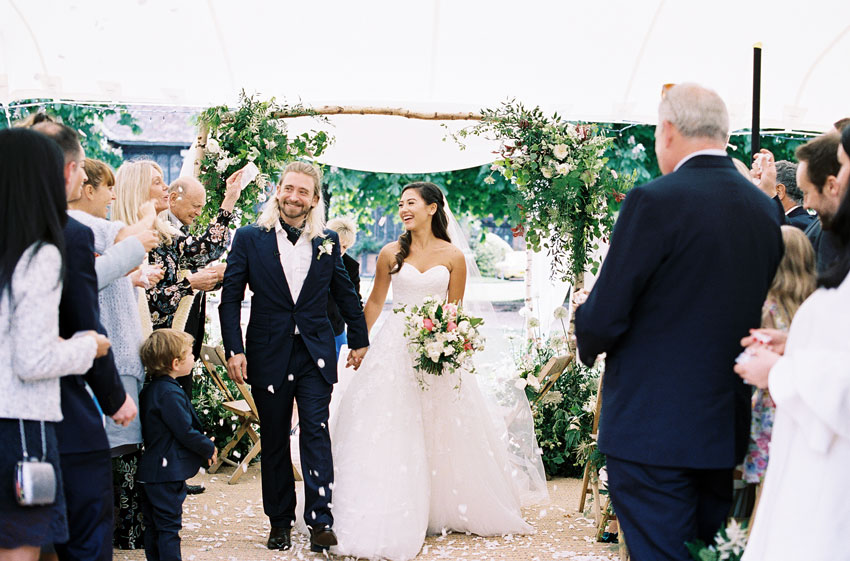 happy-married-couple-walking-down-aisle-with-wedding-guests