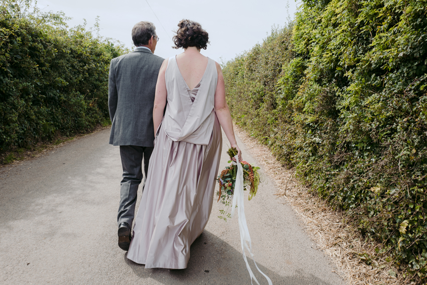 man and woman in dress holding bouquet walking down country path