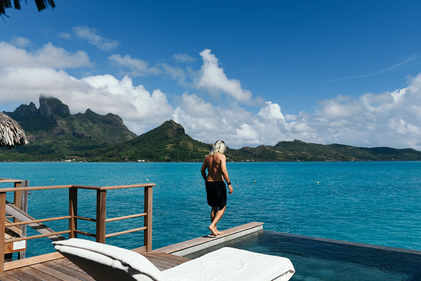 man-standing-on-plank-over-blue-water-in-Bora-Bora