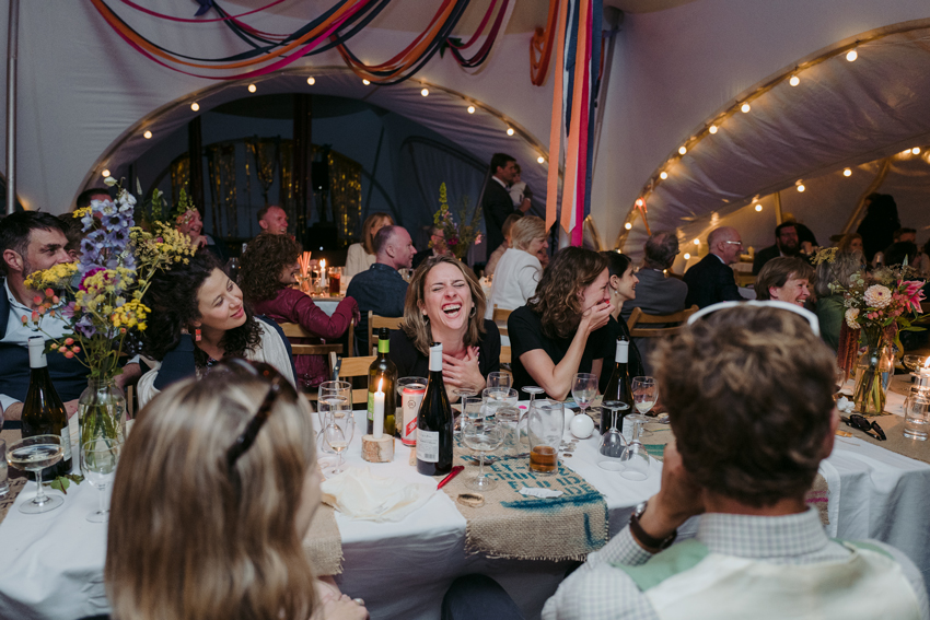 wedding guests sitting at table in marquee