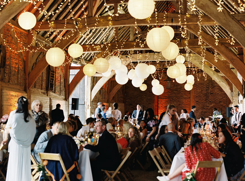 wedding-guests-sitting-in-barn-decorated-with-lights