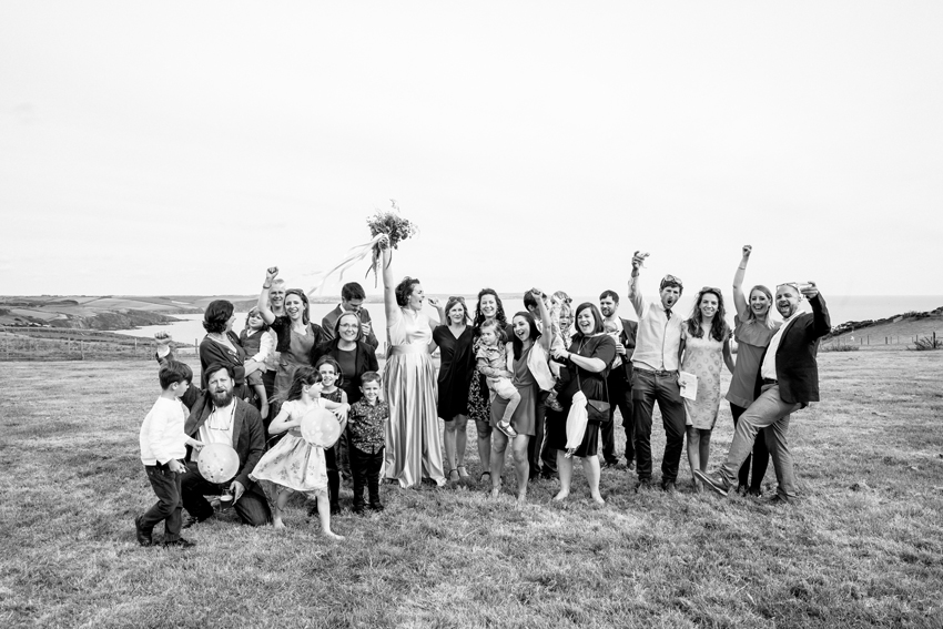 wedding party standing together in field cheering