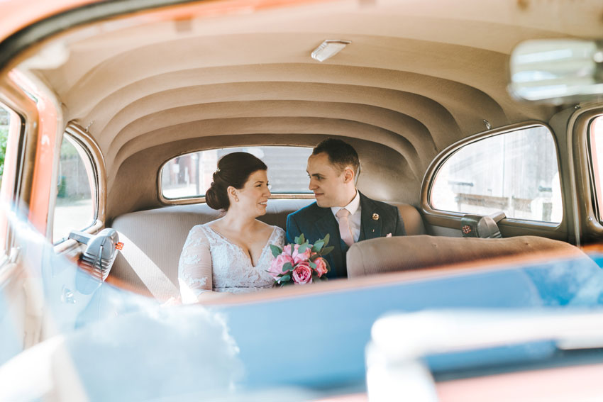 bride-and-groom-sit-in-back-of-wedding-car