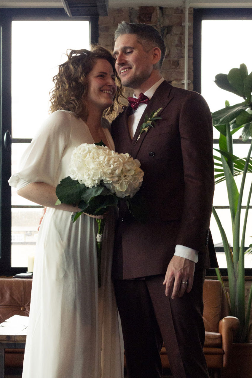 married-couple-in-wedding-dress-and-suit-holding-large-white-flowers