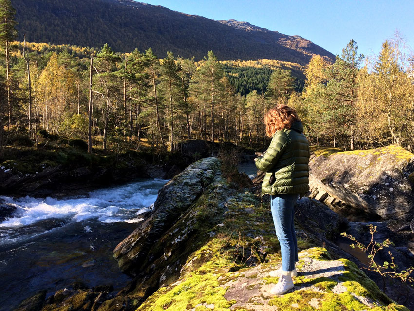 woman-stands-on-edge-of-river-in-norwar