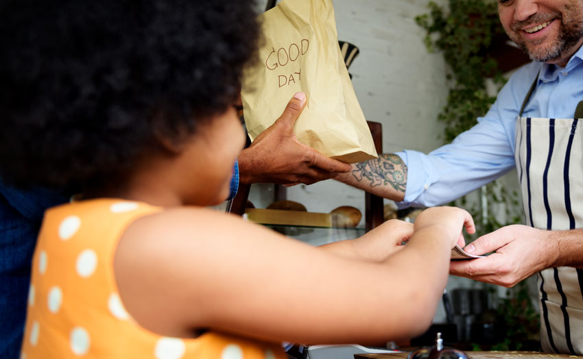 little-girl-gives-money-to-man-wearing-apron