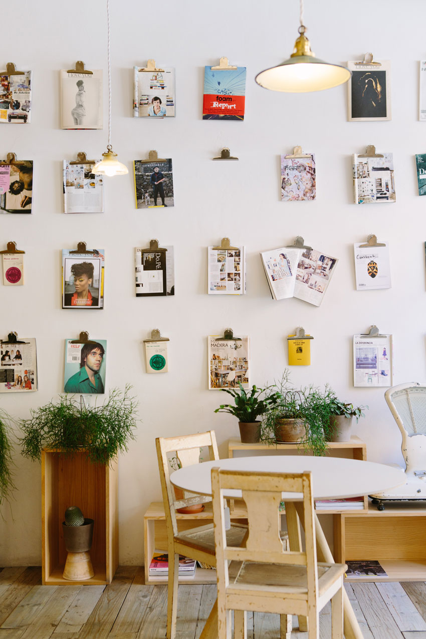 table-and-chairs-in-cafe-with-magazines-on-wall