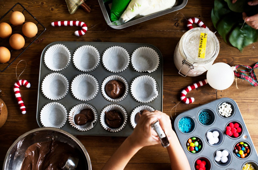 child-putting-cake-mix-in-muffin-tins-on-christmas-table