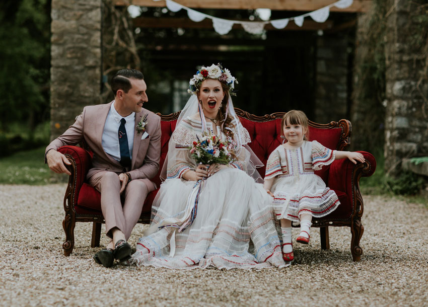 man-in-pink-suit-woman-in-wedding-dress-holding-flowers-with-little-girl-on-red-sofa