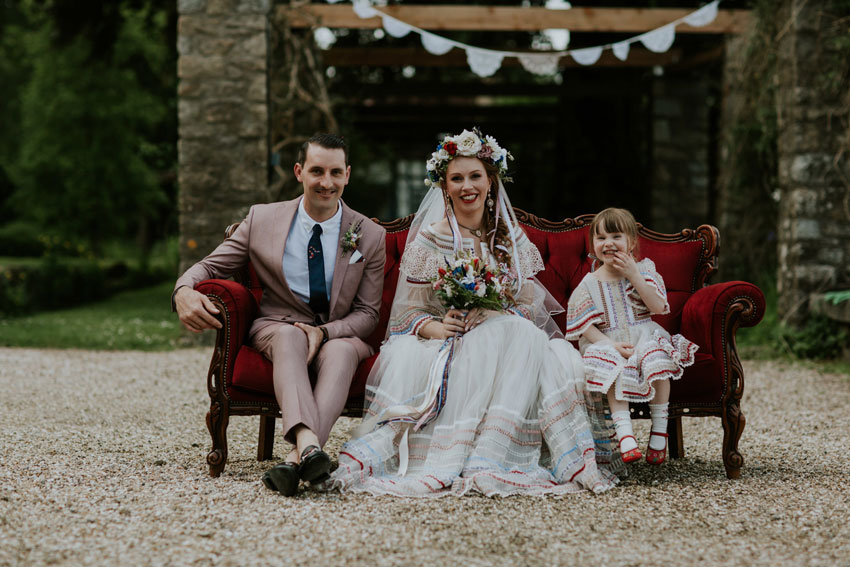 man-in-pink-suit-woman-in-wedding-dress-with-little-girl-on-red-seat