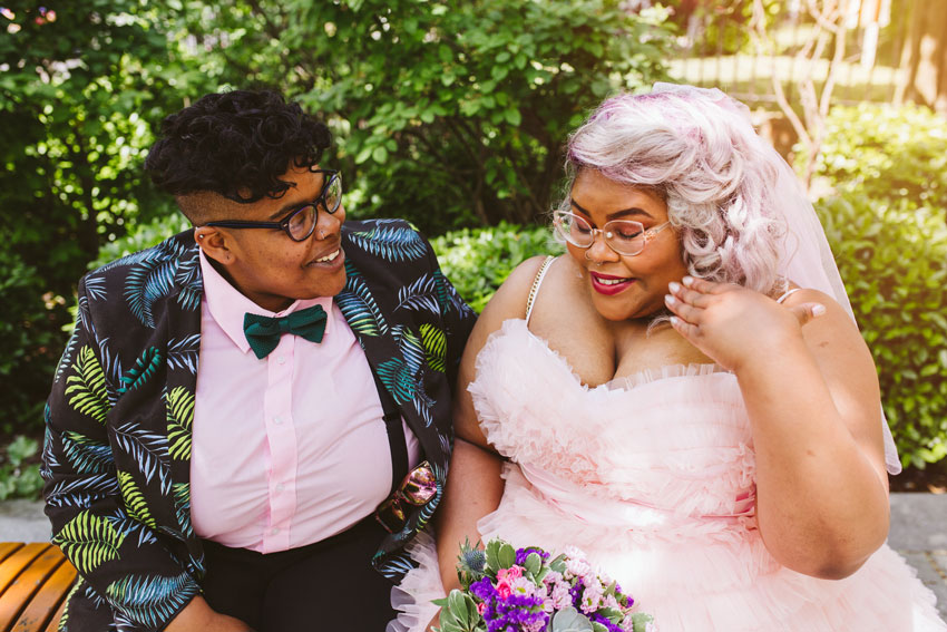 smiling-lesbian-couple-sitting-on-wall-lgbt-wedding-london