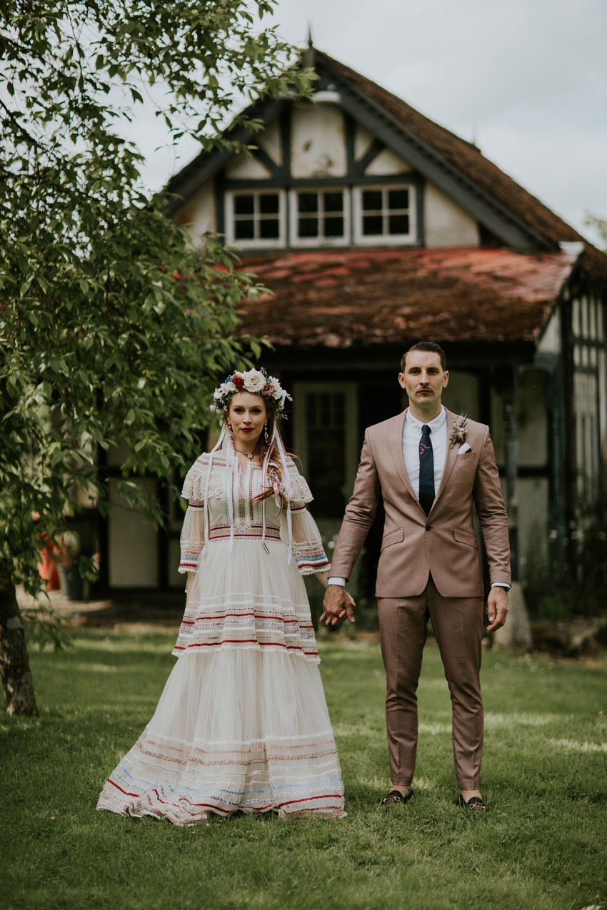woman-in-wedding-dress-holding-hands-with-man-in-pink-suit
