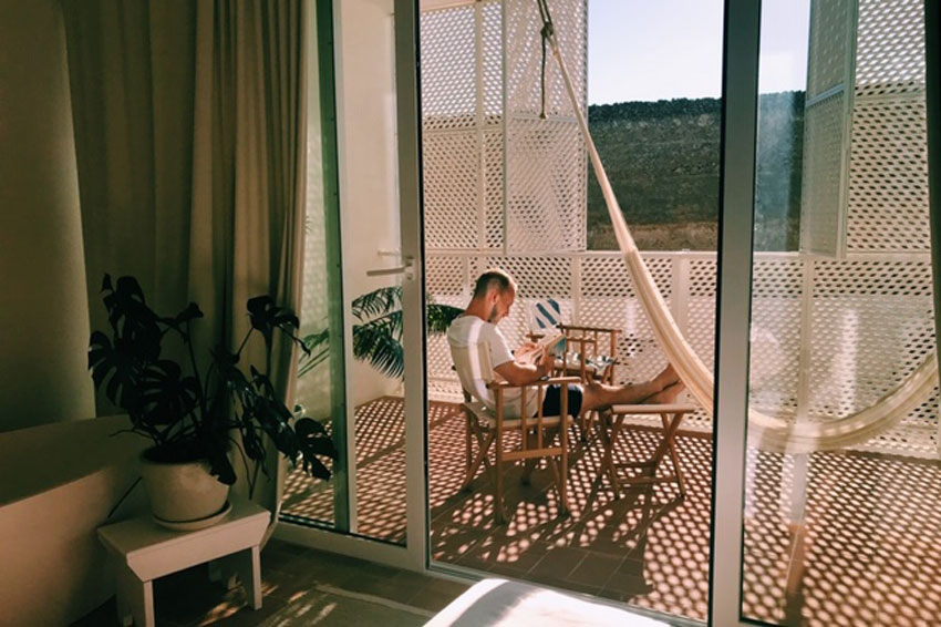 man reading book on balcony of hotel in portugal - honeymoon fund