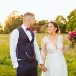 bride groom in sunlit field holding hands