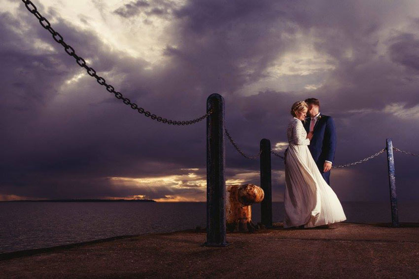 wedding couple with stormy cloud backdrop lobster shack whitstable