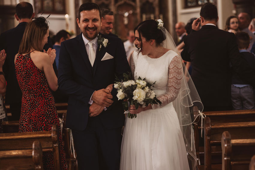 couple smiling down aisle of church after getting married