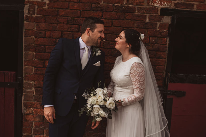 married couple smiling at each other bride holding flowers